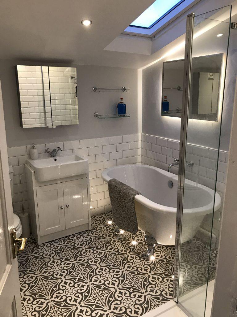 A black and white bathroom with lots of natural light and sophistication. Includes a sink and standalone tub.
